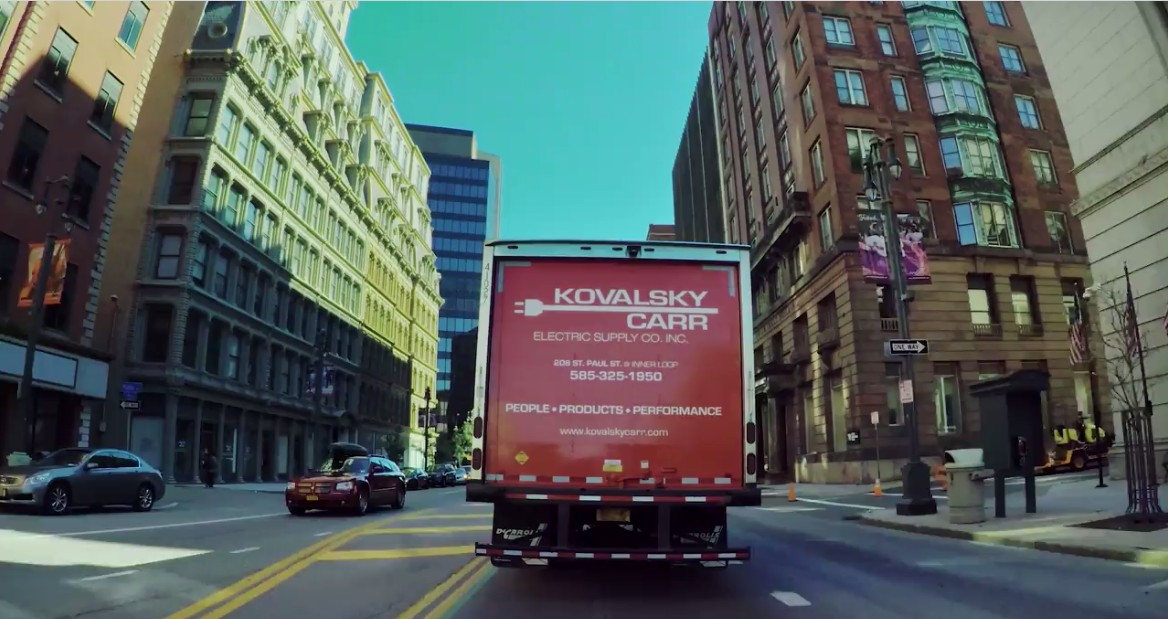 Kovalsky Carr delivery truck with logo on back, driving through downtown Rochester, NY